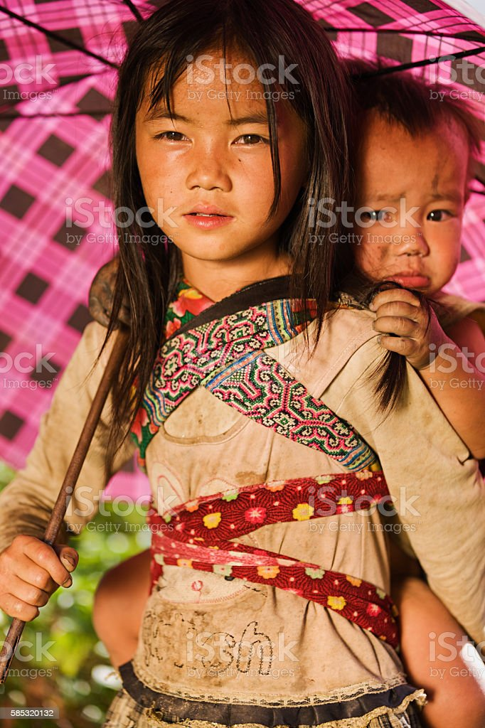 Vietnamese little girl carrying her little brother near Sapa town stock photo