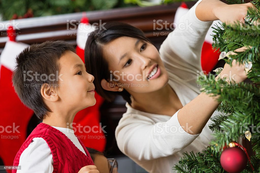 People Decorating For Christmas vietnamese mom decorating christmas tree with young son stock