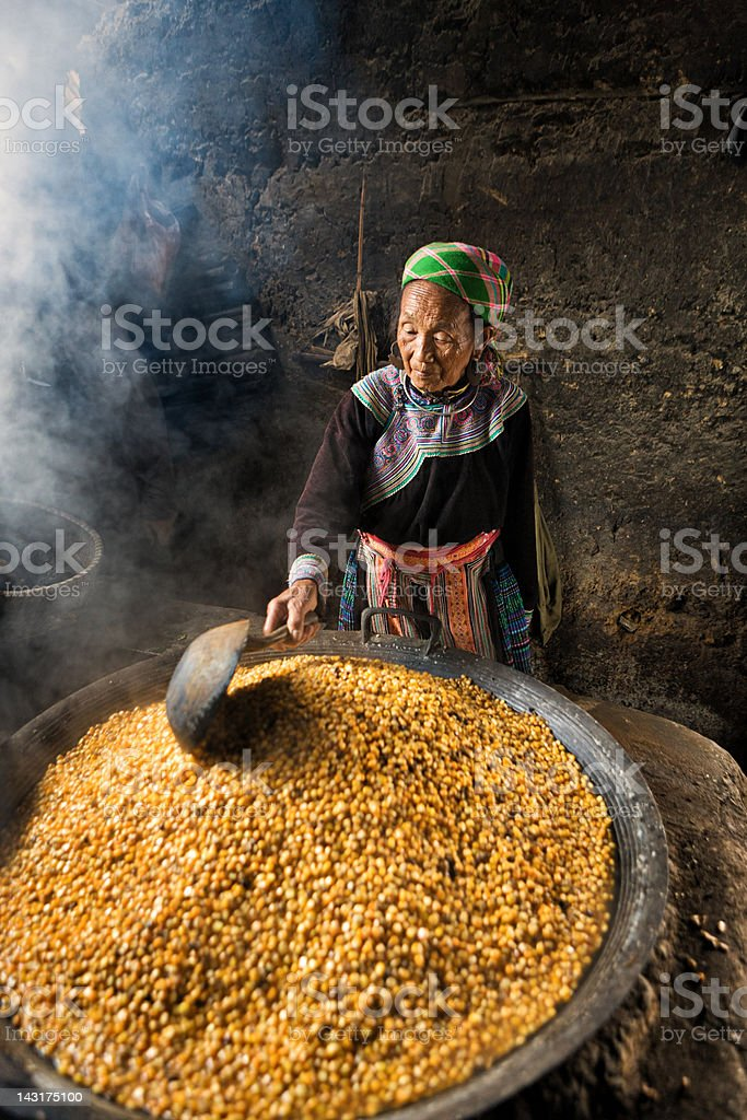 Vietnamese old woman from Flower Hmong Tribe preparing corn wine stock photo