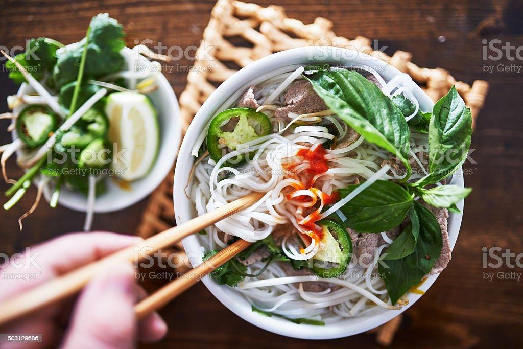 vietnamese pho with spicy sriracha sauce shot top down stock photo