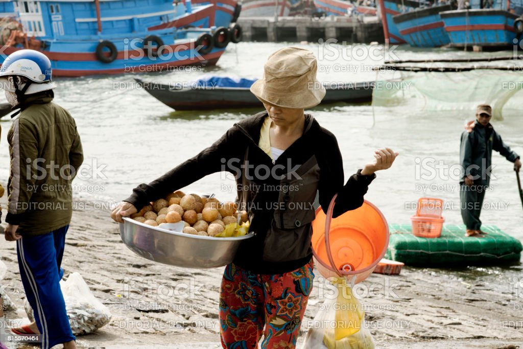 Vietnamese woman carrying a large bowl with deep fried sweet bread stock photo