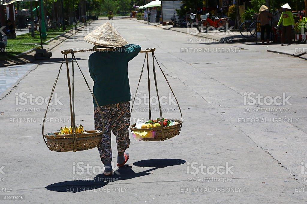 Vietnamese woman carrying fruits stock photo