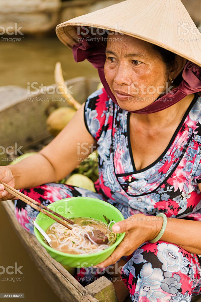 Vietnamese woman eating Pho - noodle soup on floating market stock photo