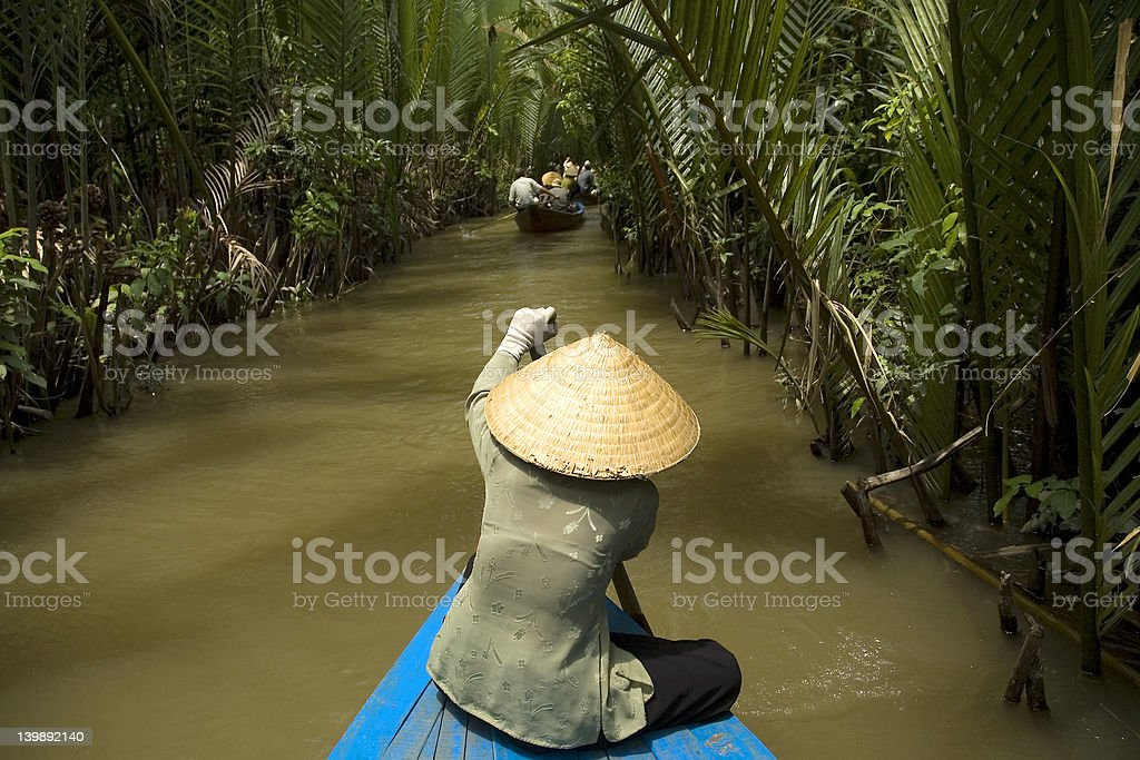 Vietnamese woman rowing a boat stock photo