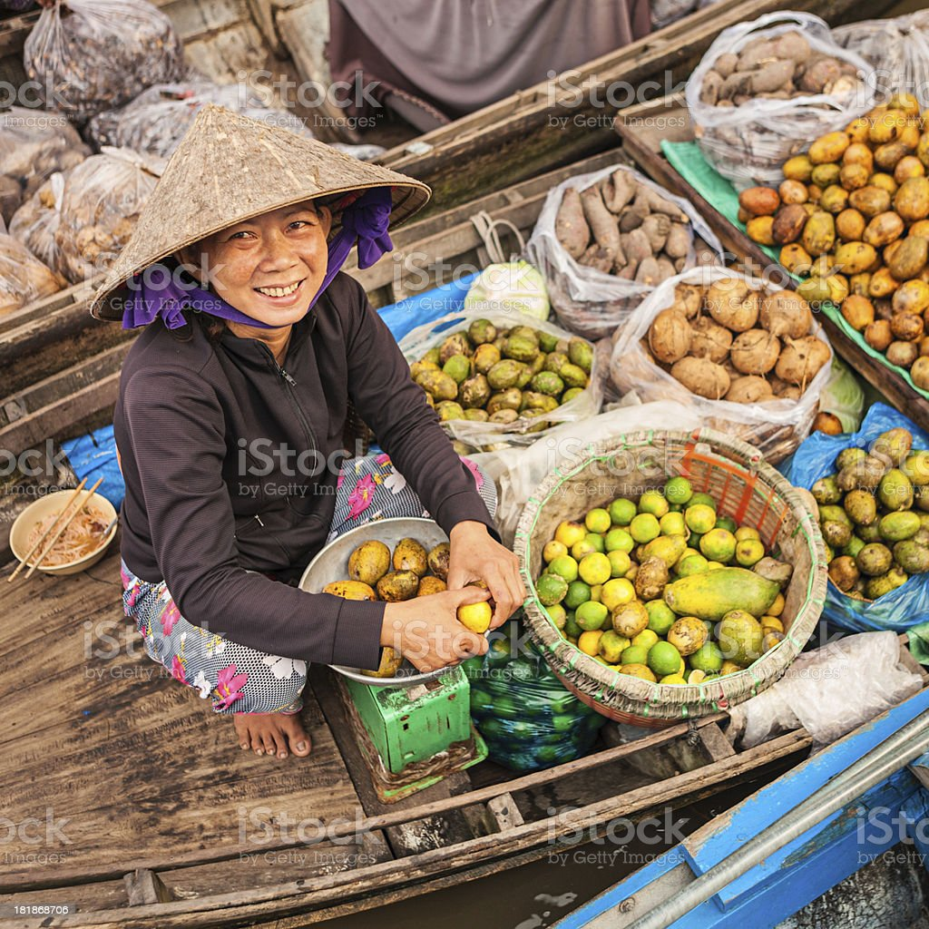 Vietnamese woman selling fruit on floating market, Mekong River Delta stock photo