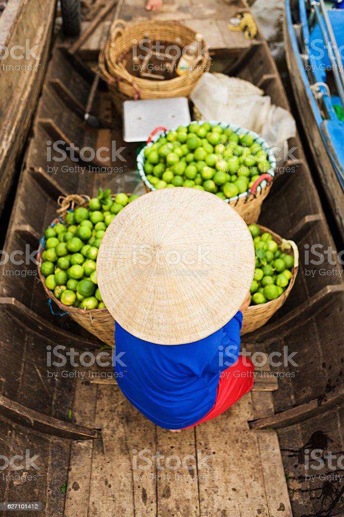 Vietnamese woman selling fruit on floating market, Mekong River Delta, stock photo