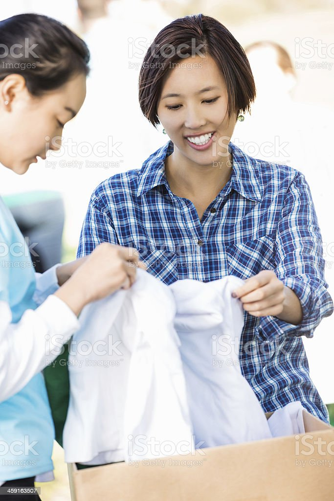 Vietnamese woman sorting clothing donations at charity drive stock photo
