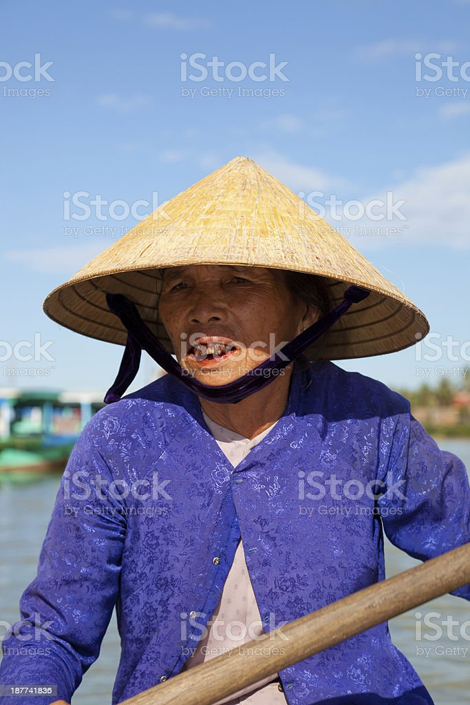 Vietnamese woman with traditional clothing driving a taxi boat, Vietnam stock photo