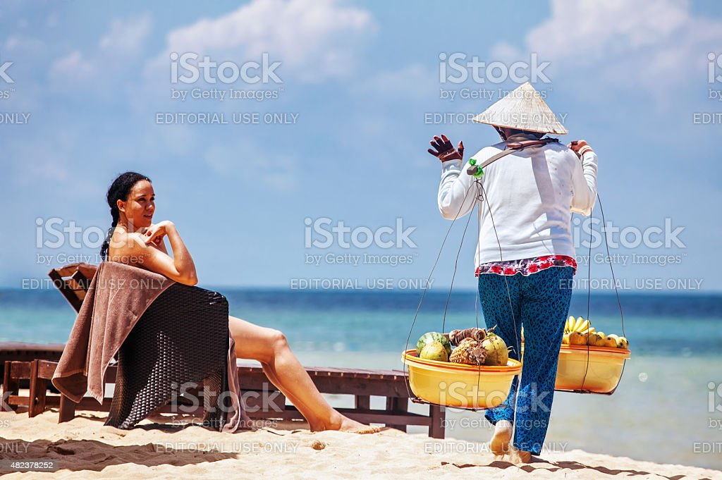 Vietnamese womans offers fruits for sale to tourists stock photo
