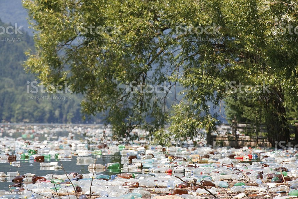 A view across a very polluted water way with plastic royalty-free stock photo