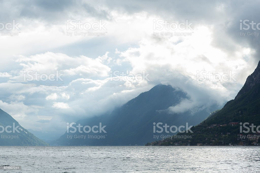 View across lake to mountains and clouds stock photo