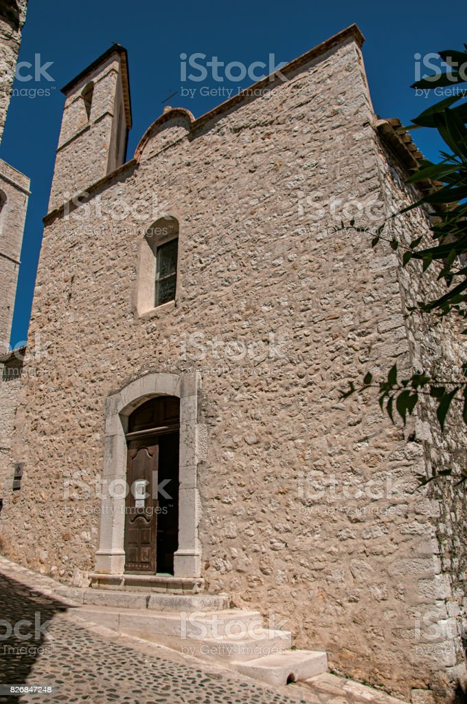 View alley and church with stone steeple tower in Saint-Paul-de-Vence. stock photo