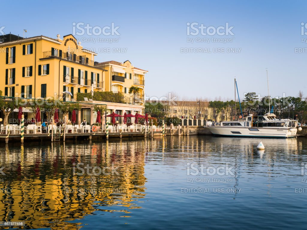 Sirmione - March 16, 2017: view at luxury hotel and boat deck at lake Garda, tourists having a lunch in restaurant of hotel. stock photo