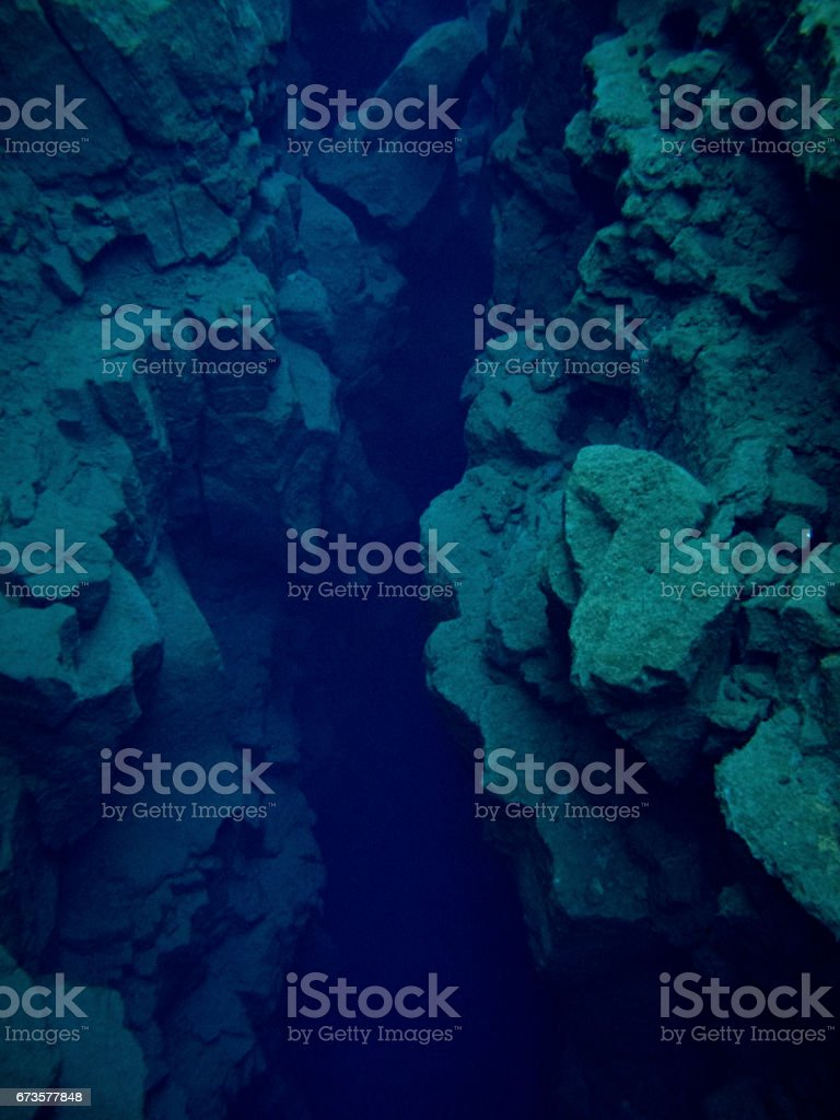 View Deep Dark Blue Abyss in Continental Split at Silfra in Deep Section at Pingvellir National Park stock photo