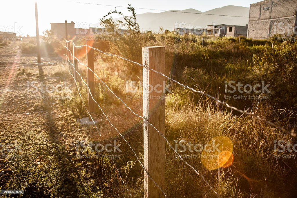 View down barbed wire fence in Mexican town. stock photo