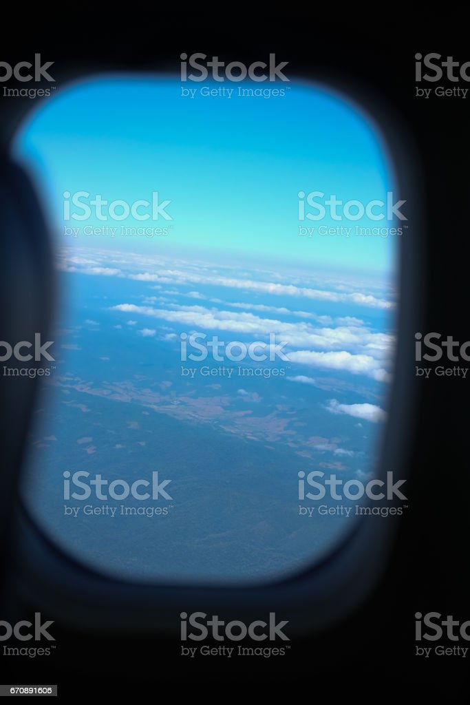View from a jet plane window high on the blue skies stock photo