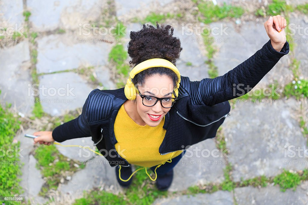 View from above of attractive young woman with yellow headphones stock photo