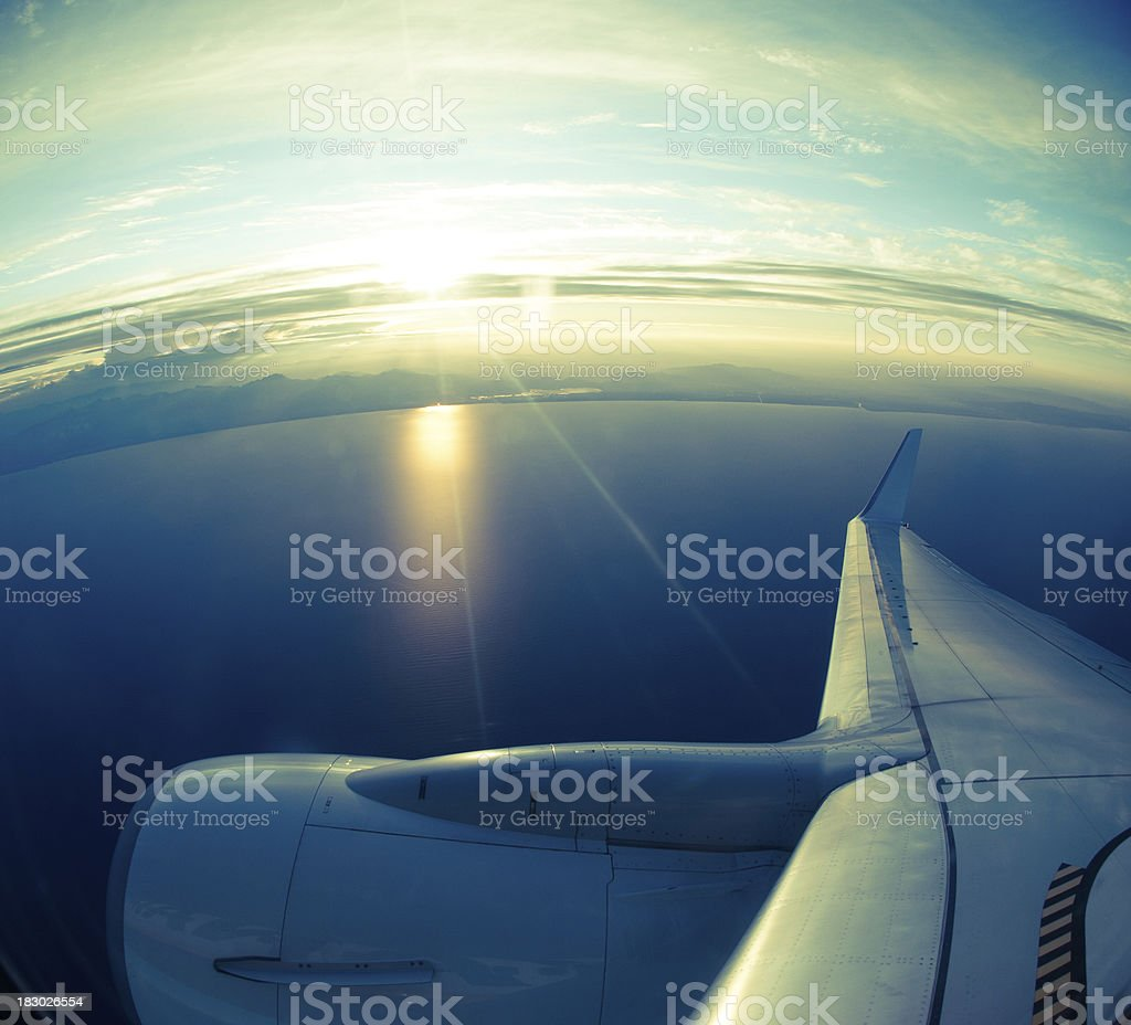 view from airplane porthole of the ocean coastline on sunset royalty-free stock photo