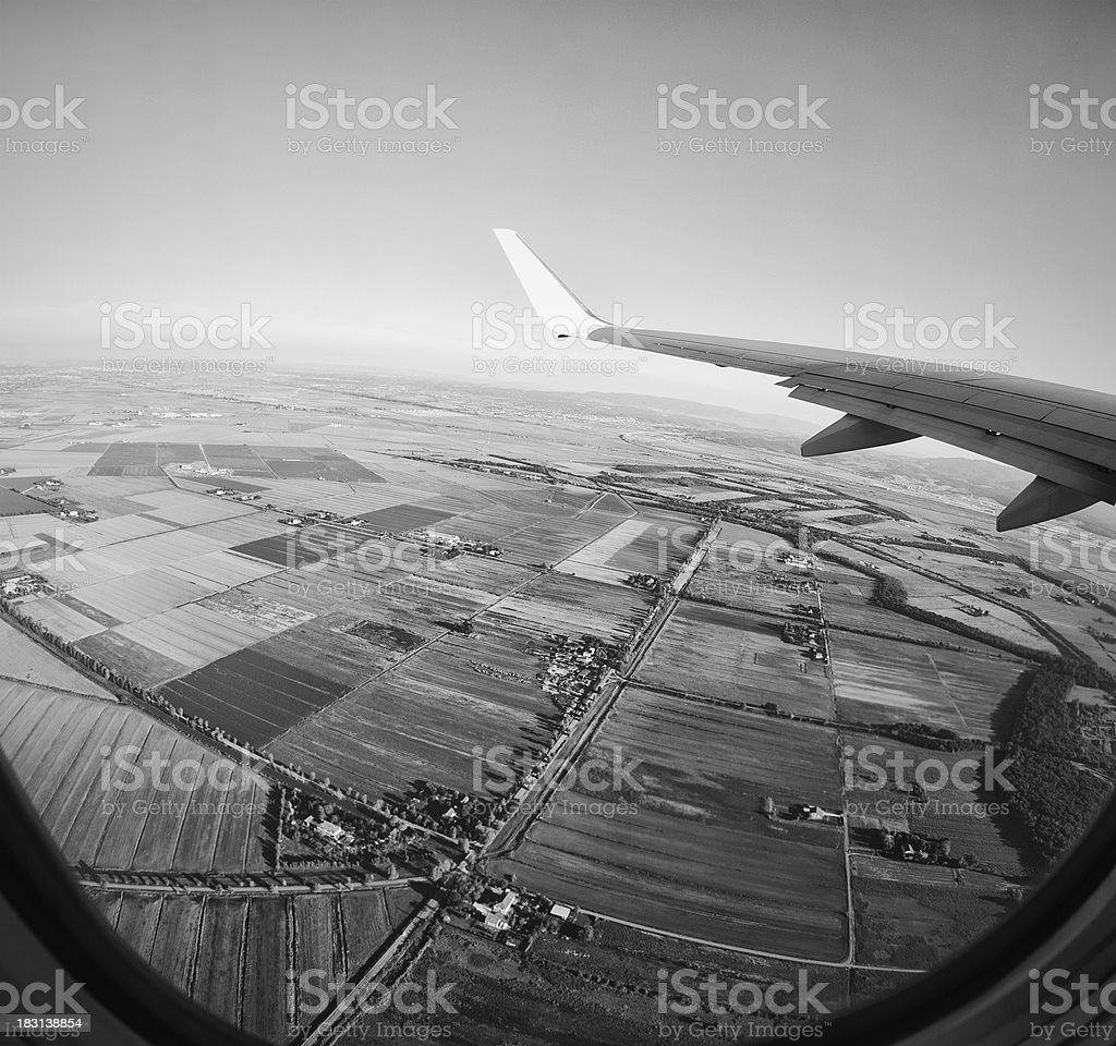 view from airplane porthole on flying at sunset - Monochrome royalty-free stock photo