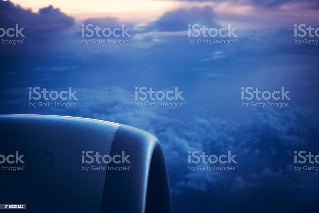 View from airplane window on sunrise sky in blue tones stock photo