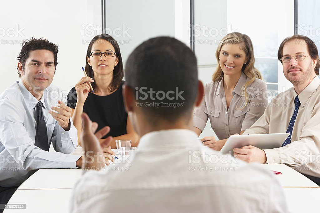 View From Behind As CEO Addresses Meeting In Boardroom royalty-free stock photo