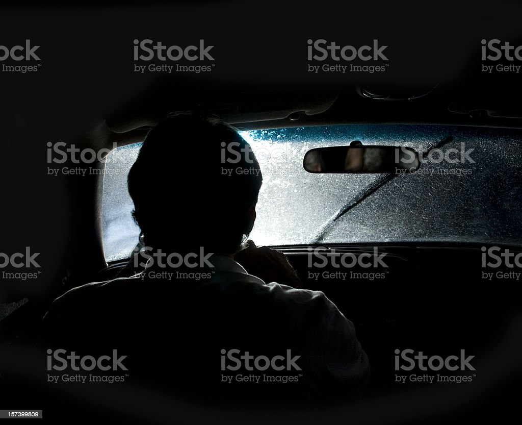 view from behind man driving at night in rain-lights glaring in stock photo