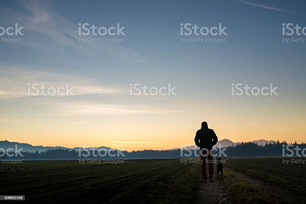 View from behind of a man walking with his black stock photo