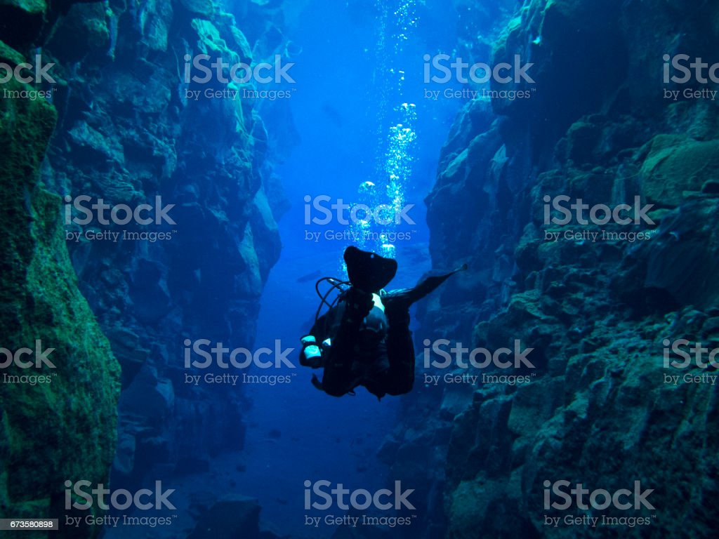 View from Behind Single Scuba Diver with Bubbles Above at Continental Split at Silfra in Deep Section at Pingvellir National Park stock photo