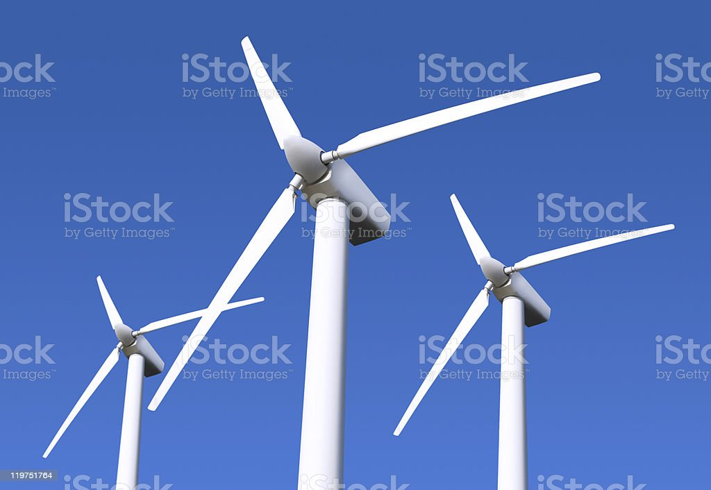View from below of 3 large, white wind turbines and blue sky royalty-free stock photo