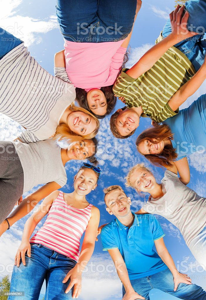 View from below of friends standing in star shape stock photo