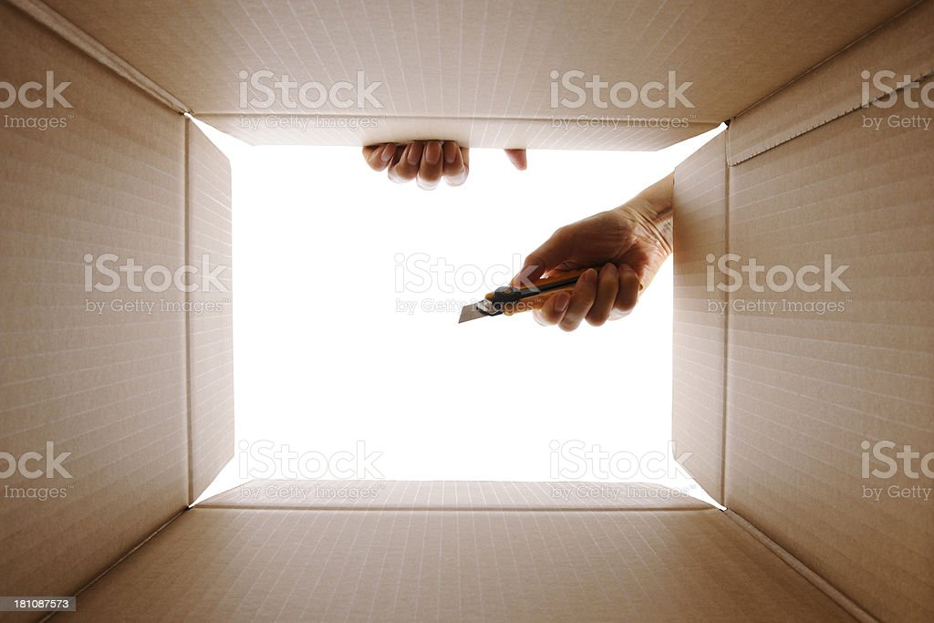 View from inside a cardboard box with using box cutter royalty-free stock photo