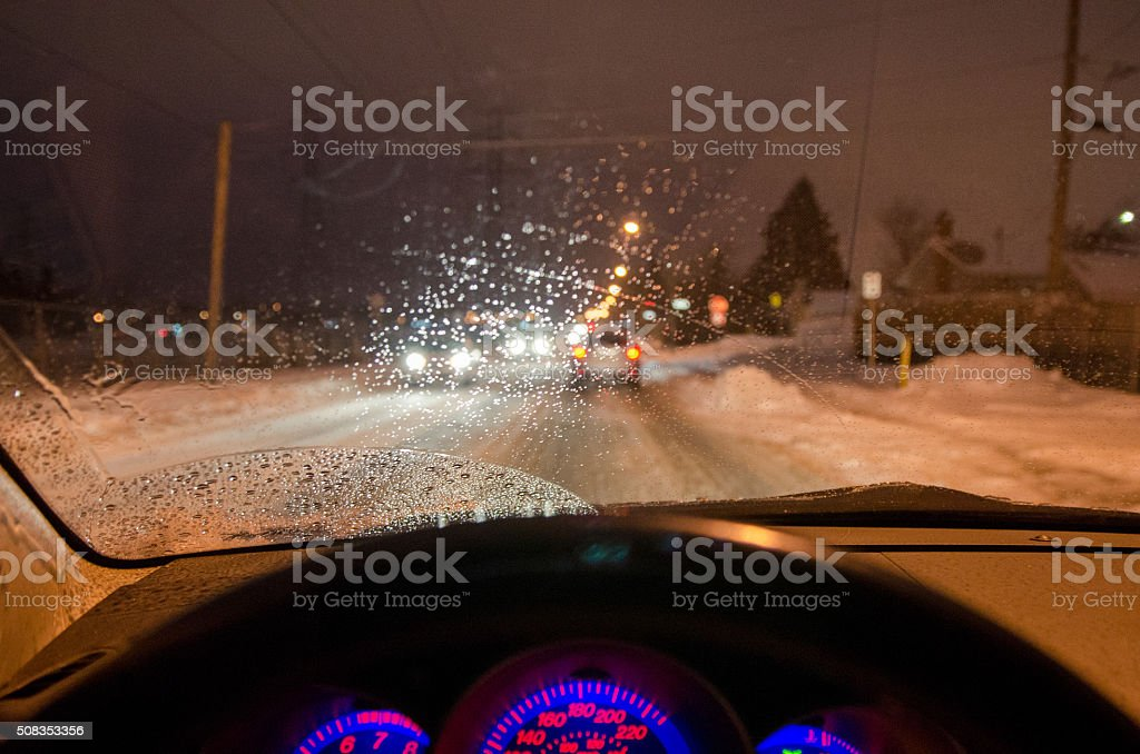 View from inside car while driving night snowstorm stock photo