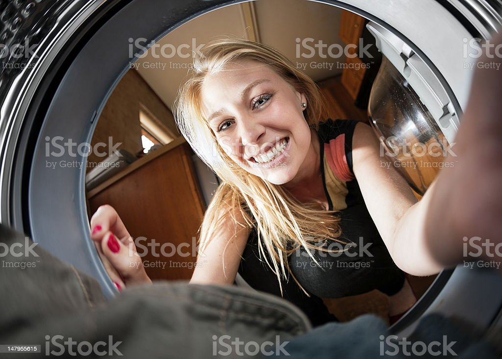 View from inside washing machine drum of smiling housewife stock photo
