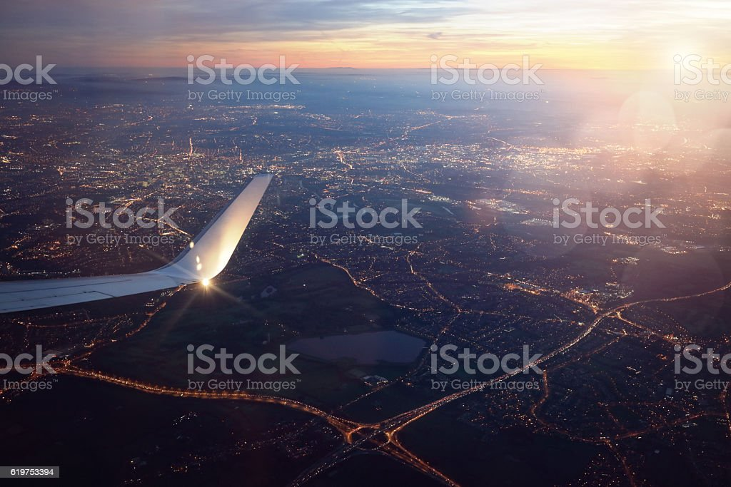 View from landing airplane window of city at sunset stock photo