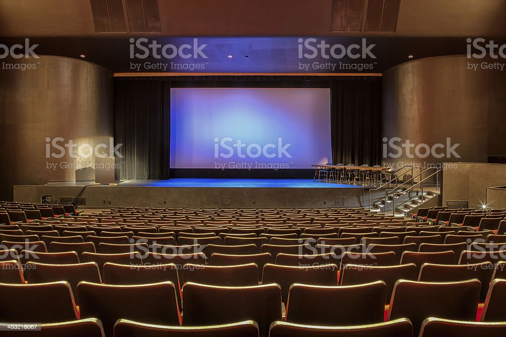 Empty auditorium with all lights on. Visible scrren in the center of...