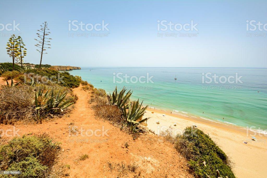 View from the cliffs to busy beach Praia do Porto de Mos near Ponta da Piedade, Lagos Algarve Portugal stock photo