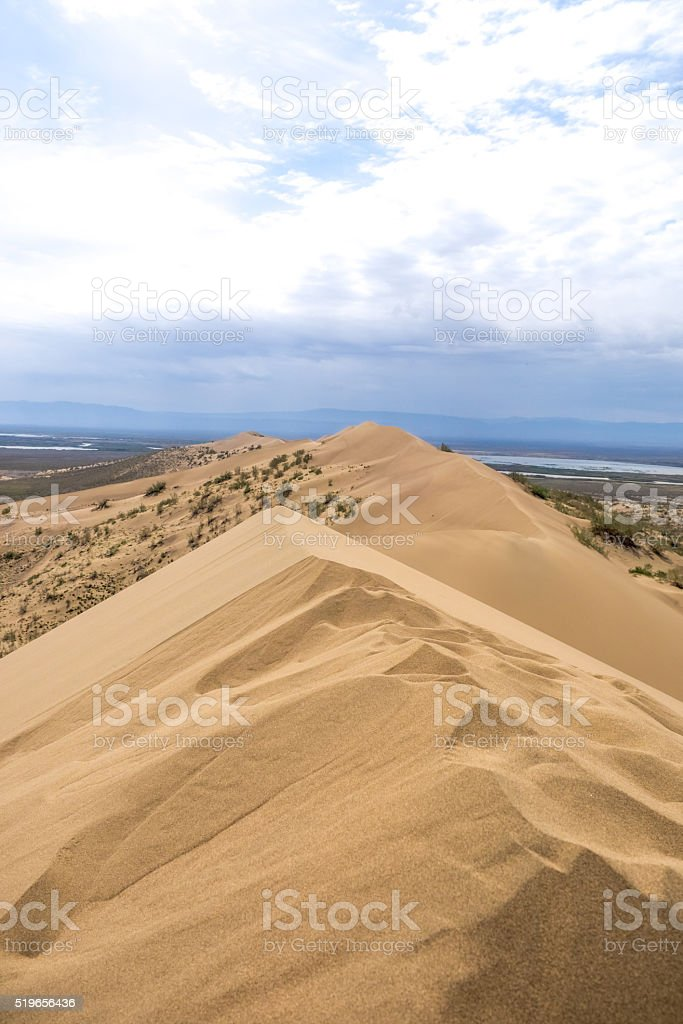 view from the dune brink on prairie and mountains stock photo
