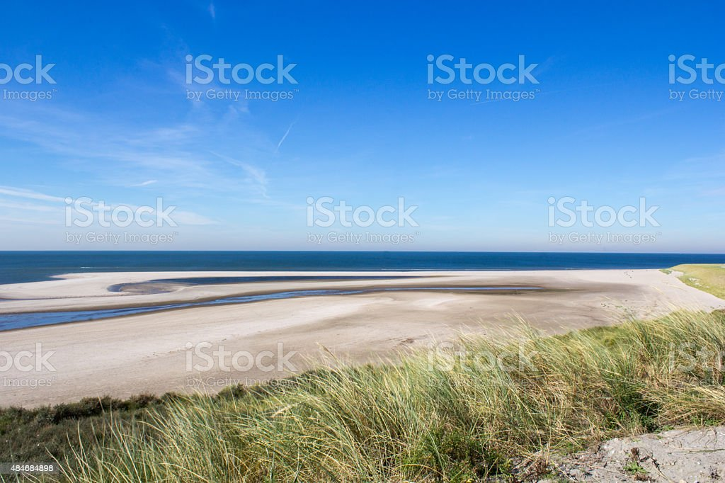 View from the dunes over the beach of the Northsea. stock photo
