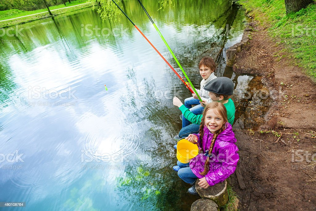 View from up of kids holding fishing tackles stock photo