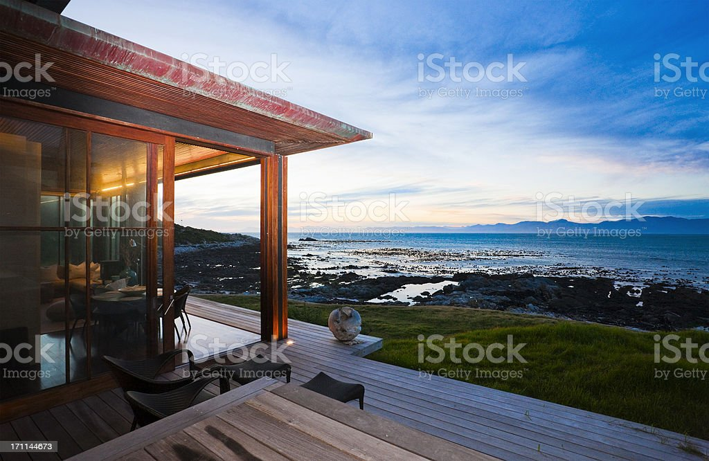 View from veranda of beach cottage over sea at sunset stock photo