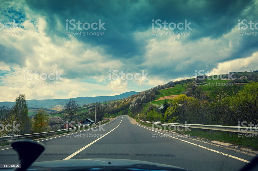 View from windscreen. Driving a car on mountain road stock photo