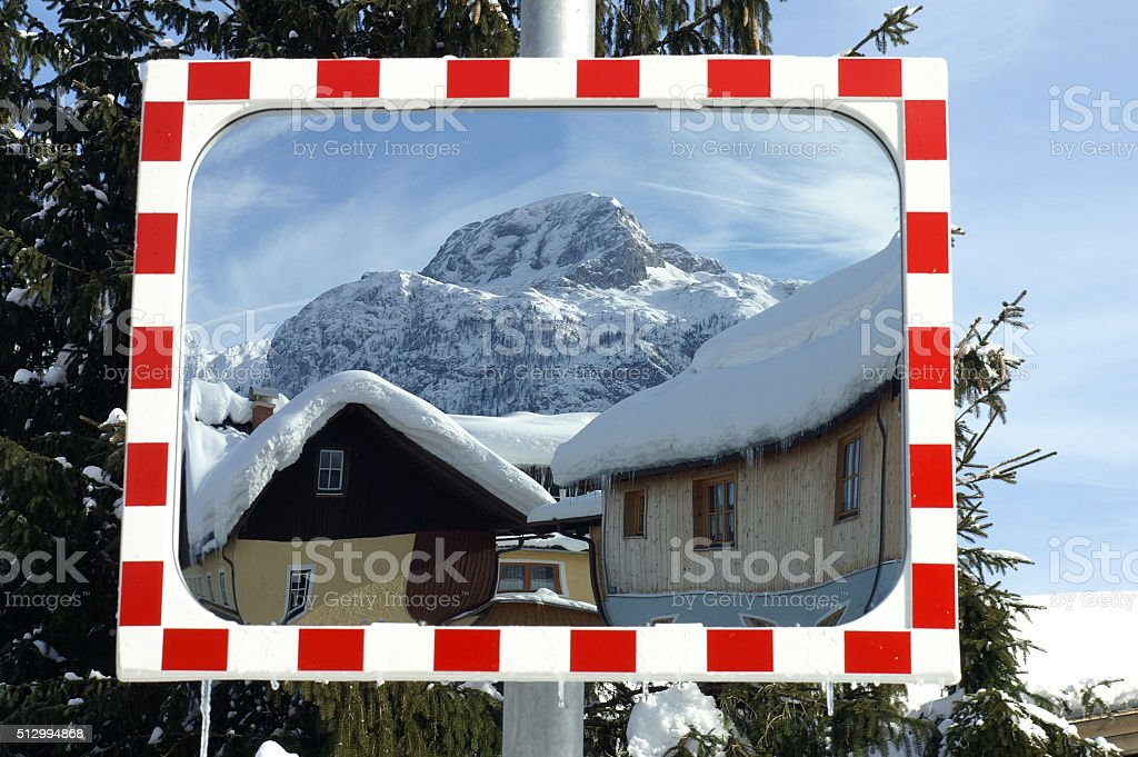 View in a mirror on a small winter village in Austria stock photo