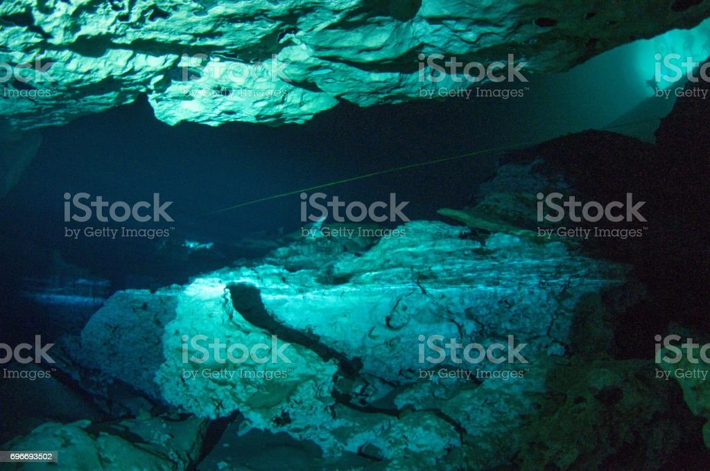 view inside long cavern space inside cenotes tulum with blue light from entrance and guide line inside cave (PADI standard) stock photo