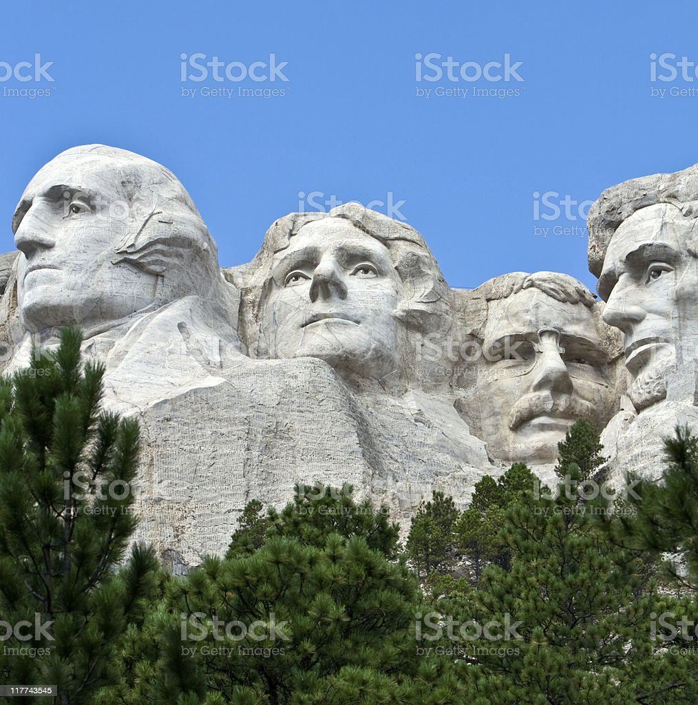 View looking up at Mount Rushmore with trees in front royalty-free stock photo