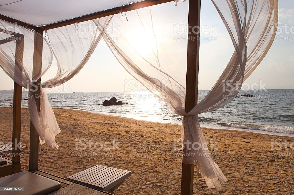View of a beach in sunset through the curtains stock photo