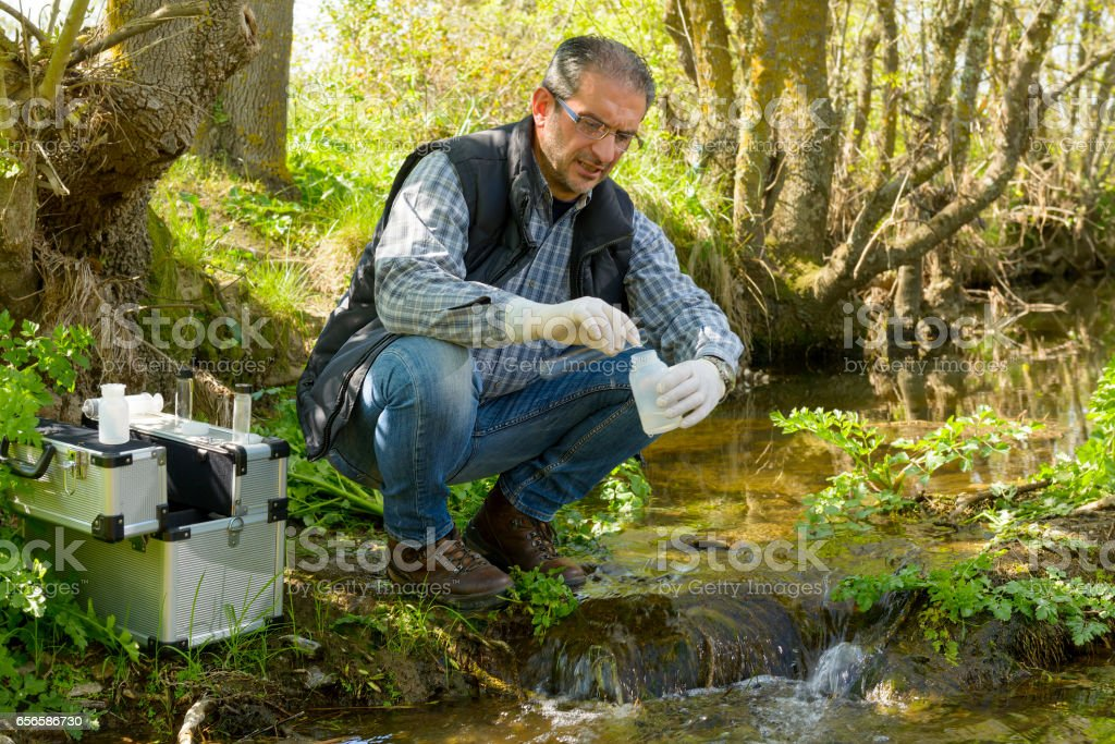View of a Biologist take a sample in a river. stock photo