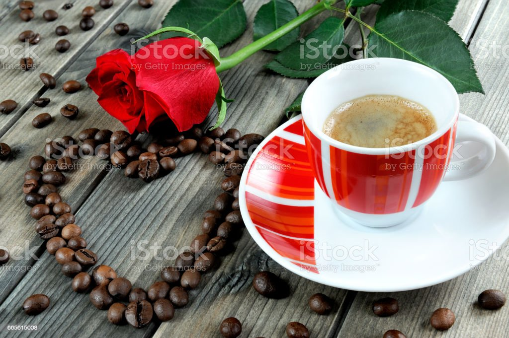 View of a coffee cup on a wooden table old adorned with a red rose and coffee beans. stock photo