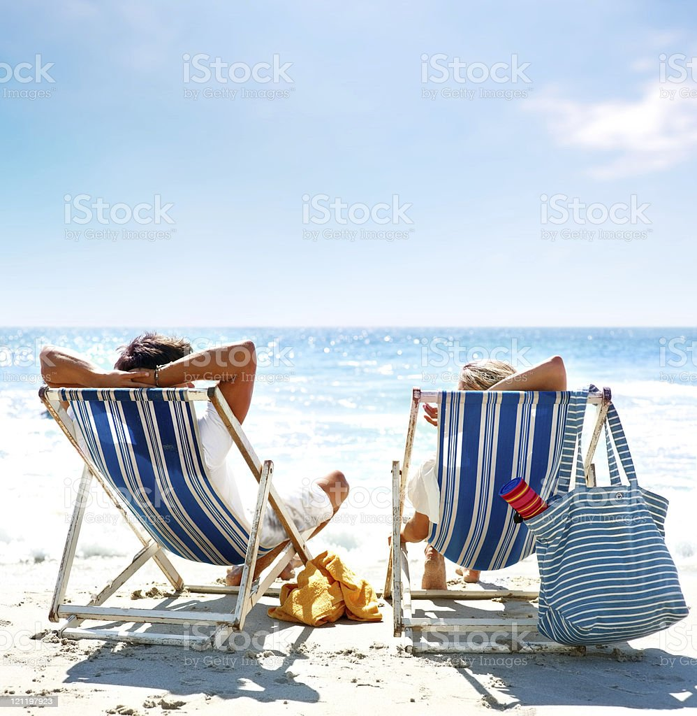 View of a couple sitting on deck chairs enjoying vacation stock photo