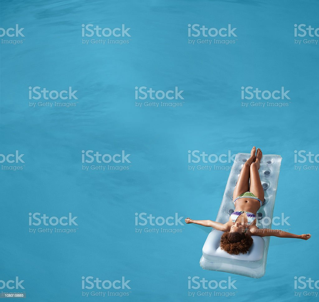 View of a female floating in swimming pool stock photo