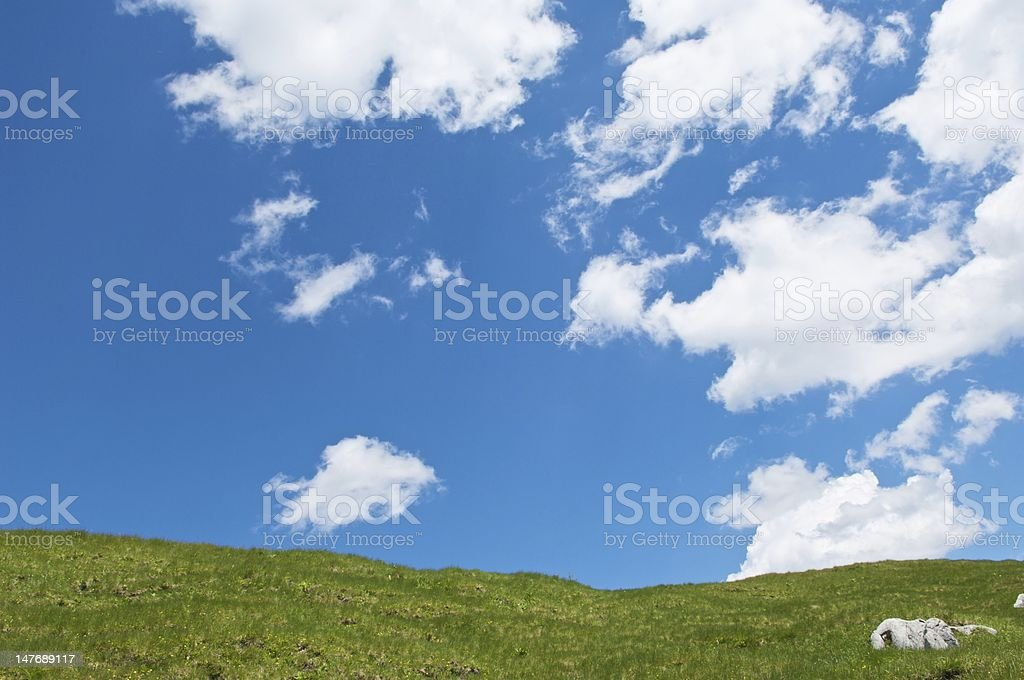 View of a Green Hill with Blue Sky and Clouds stock photo